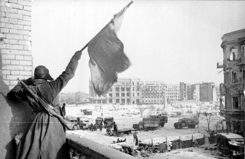Soviet soldier waving the Red Banner over the central plaza of Stalingrad in 1943. Photograph taken by Georgii Zelma.